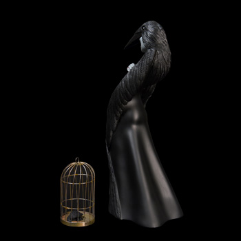 Melancholic beauty and death cloaked in feathers. A headdress with shiny black eyes and sharp beak is mounted over petite downcast features.