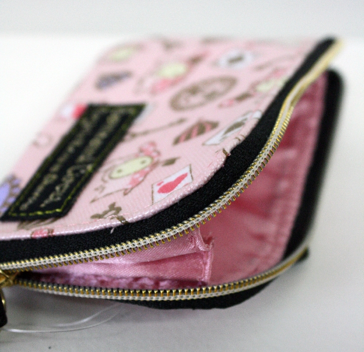 This adorable coin purse measures 4.5 inches in length and comes with a black wristlet to hook key chains onto. Zips open to reveal soft pink lining.